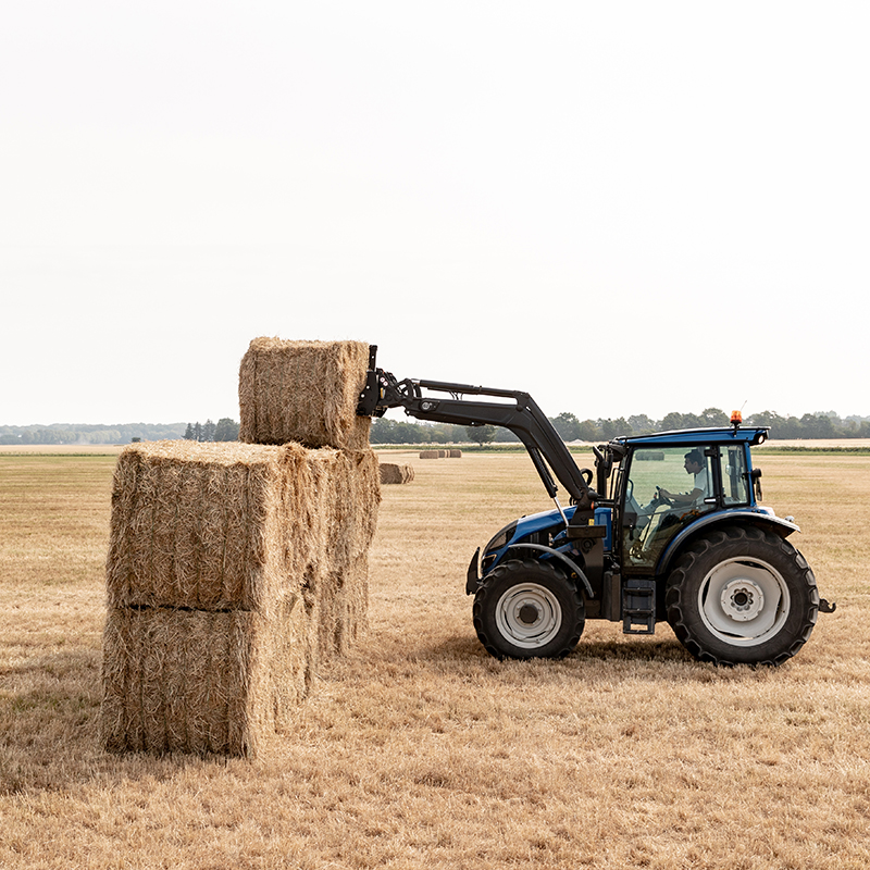 valtra a series tractor with frontloader lifting hay bales